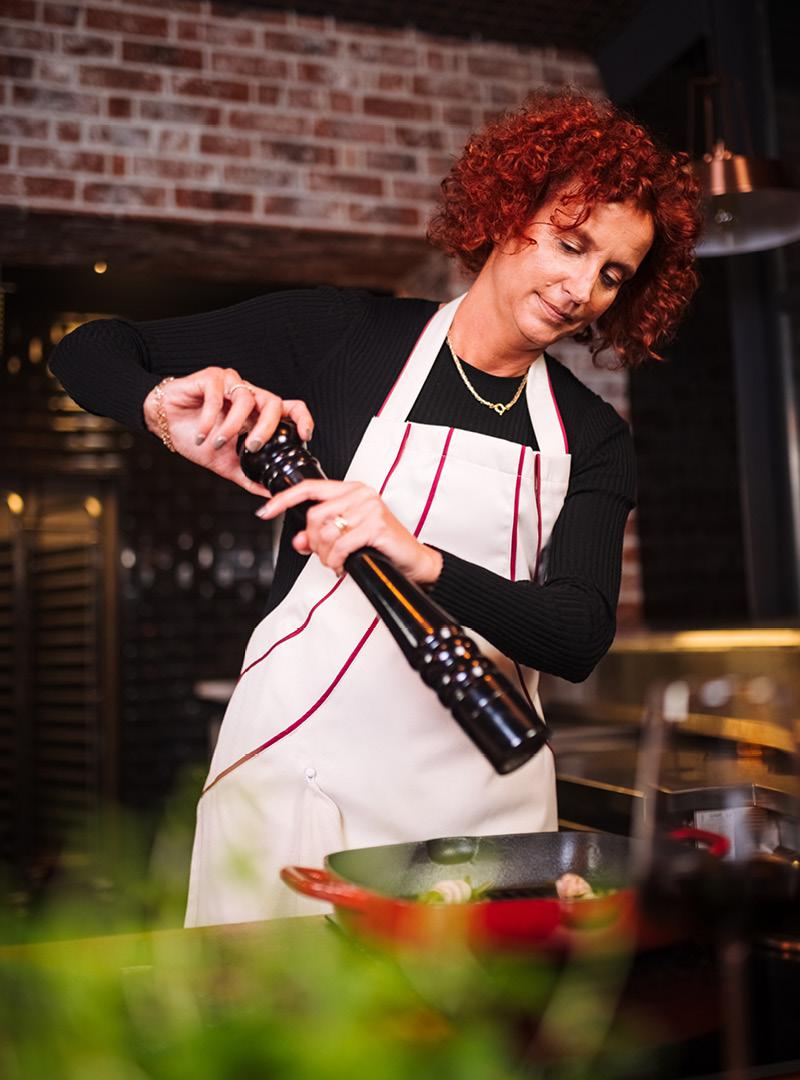 le tablier | Frau beim Kochen mit Pfeffermühle und beiger Schürze