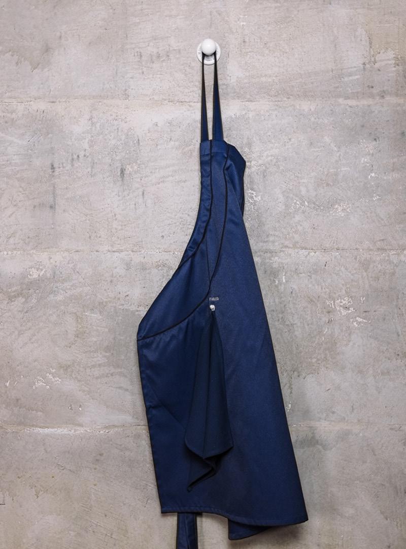 le tablier | dunkelblaue Schürze an weißem Kleiderhaken vor einer Betonwand