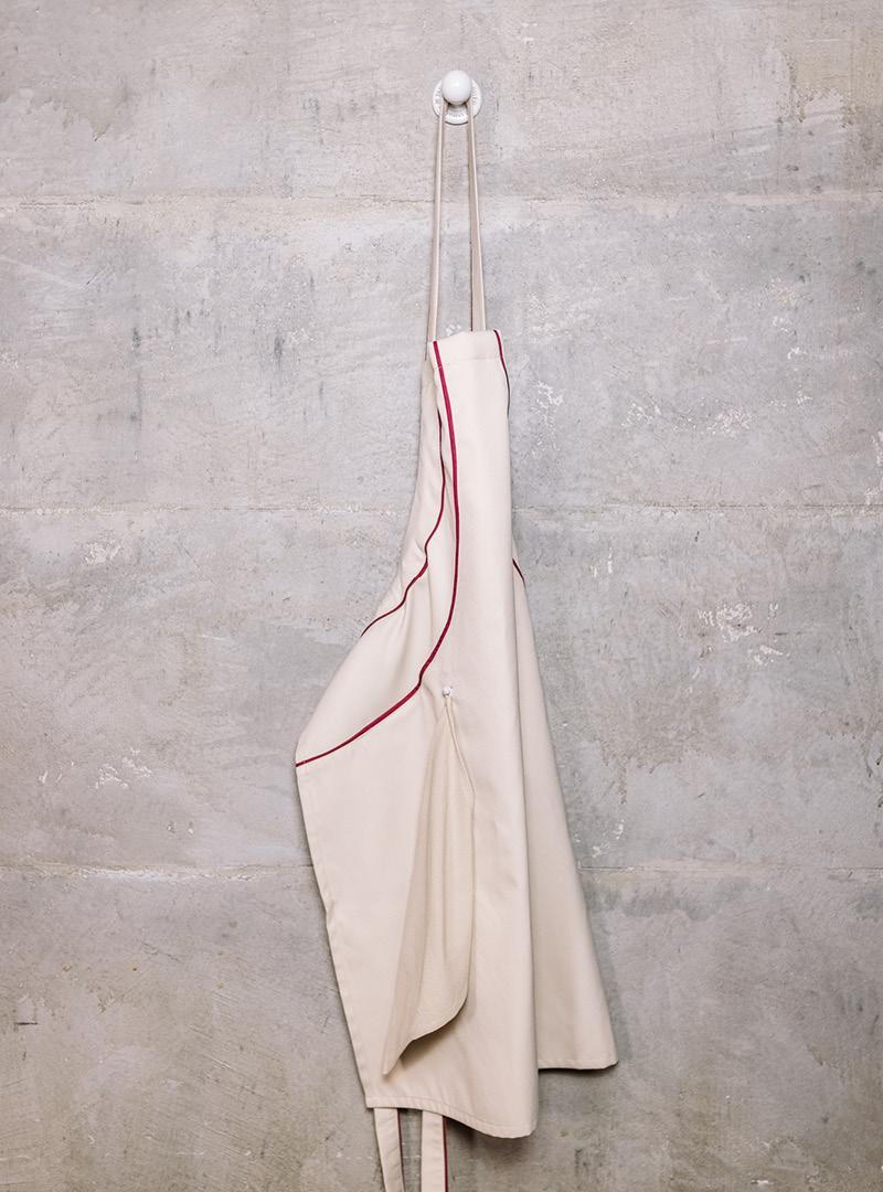 le tablier | beige Schürze an weißem Porzellanhaken an einer Betonwand