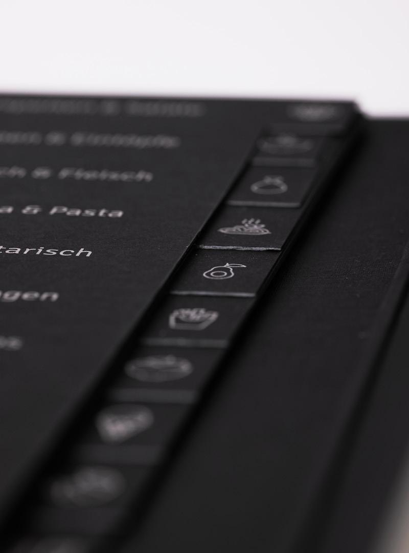 le tablier   schwarzes Register mit silbener Schrift und Icons in einer Nahaufnahme