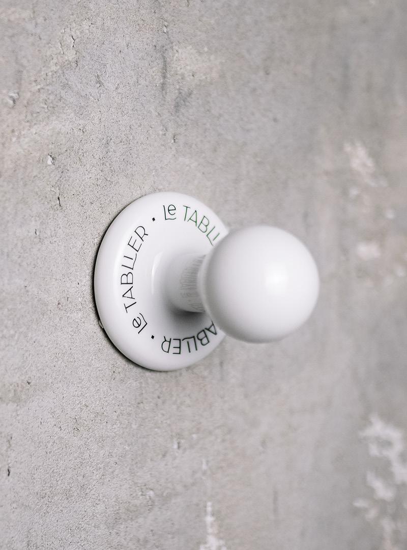 le tablier | Betonwand mit einem weißen Kleiderhaken mit Beschriftung