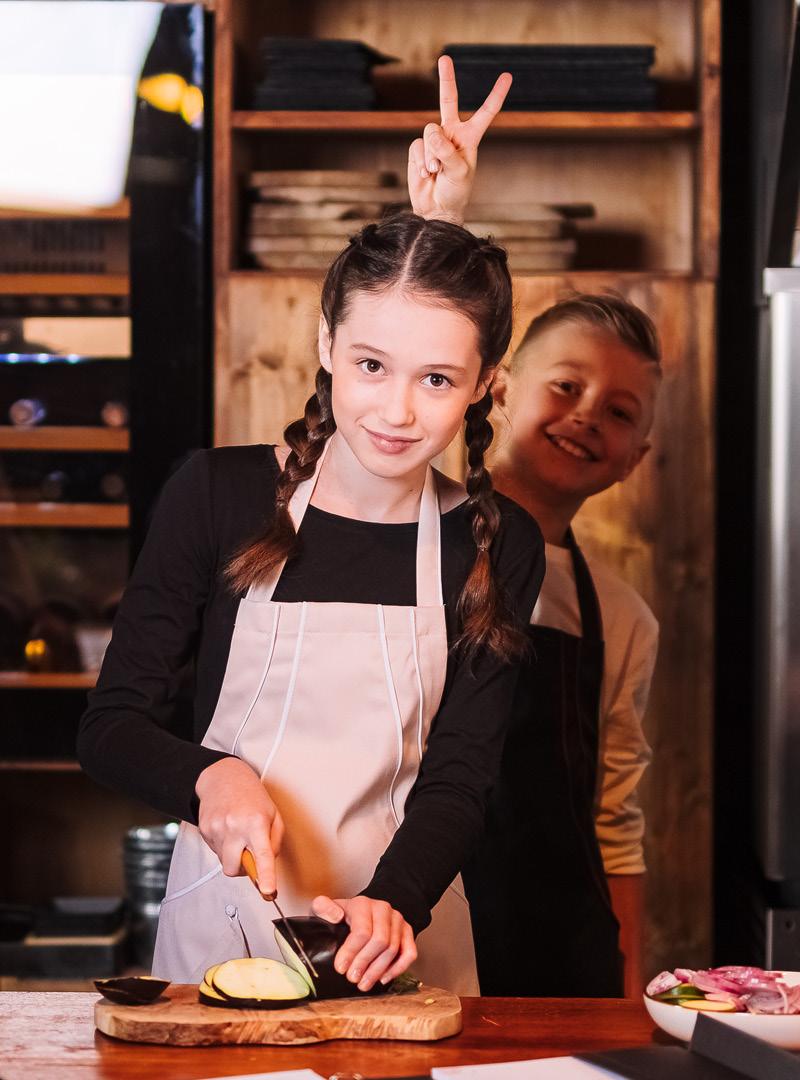 le tablier | dunkelhaariges Mädchen mit rosa Schürze in einer Küche beim Gemüse schneiden