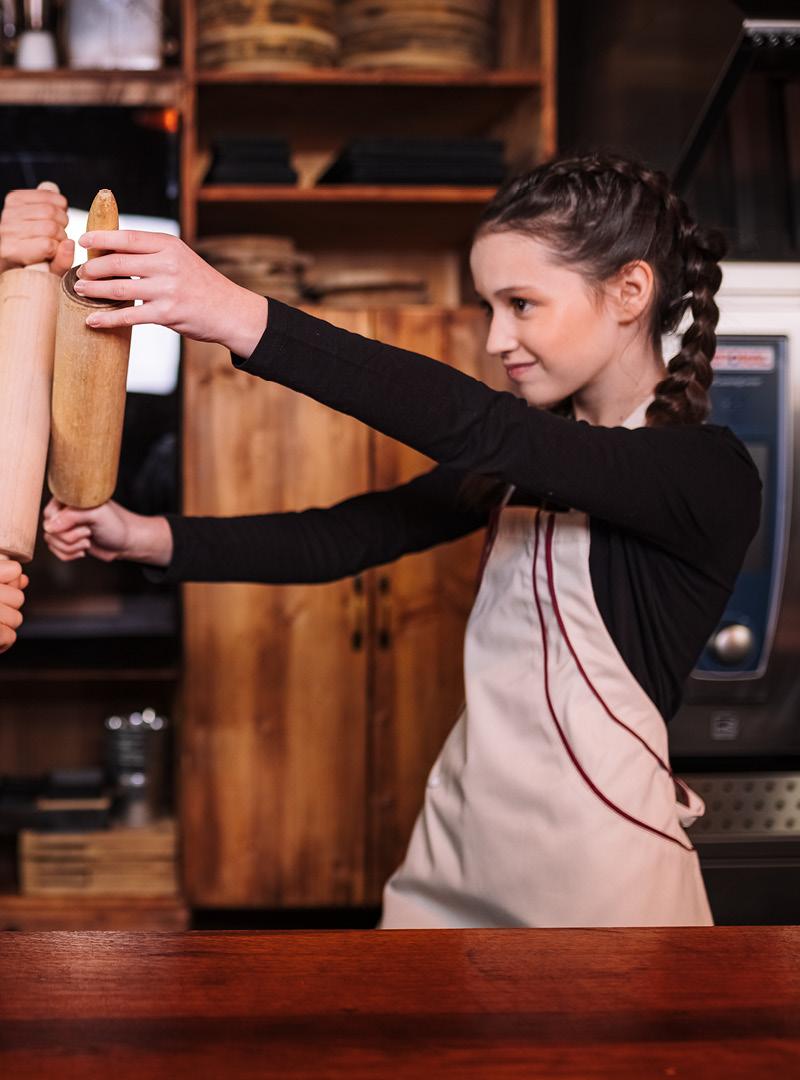 le tablier | Mädchen mit Zöpfen in der Küche mit beiger Schürze