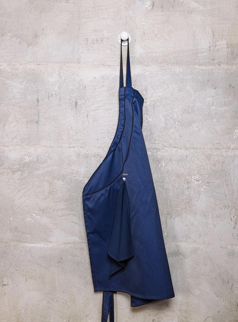 le tablier | dunkelblaue Schürze an Haken mit Abtrockentuch vor Betonwand