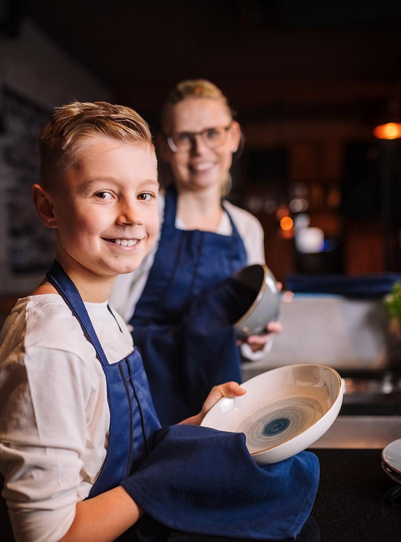 le tablier | blonder Junge mit Mutter beim Abspülen mit blauen Schürzen