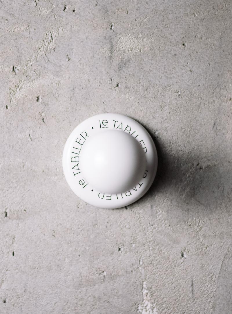 le tablier | Frontalansicht eines weißen Porzellanhakens mit aufgedruckter schwarzer Schrift in einer Betonwand