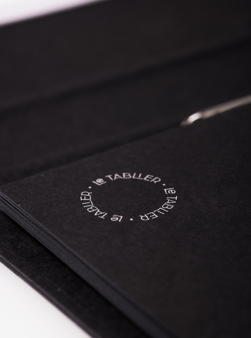 le tablier   schwarzes Register mit silbener Schrift in Nahaufnahme
