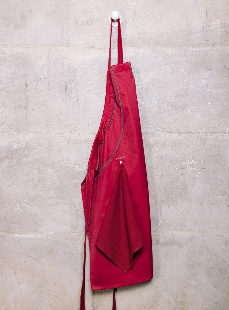 le tablier | dunkelrote Schürze an Kleiderhaken an Betonwand hängend