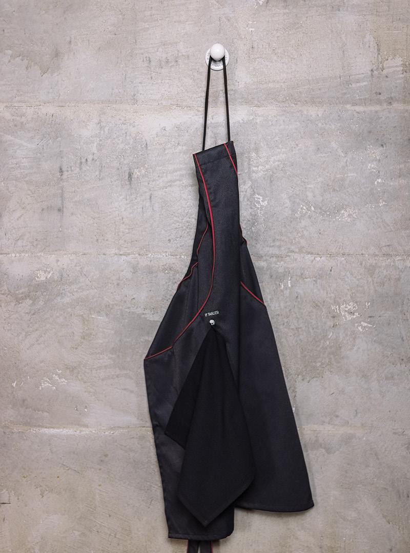 le tablier | schwarze Schürze an weißem Haken vor Betonwand
