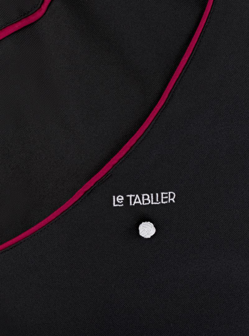 le tablier | schwarzer Stoff mit roten Elementen in Nahaufnahme