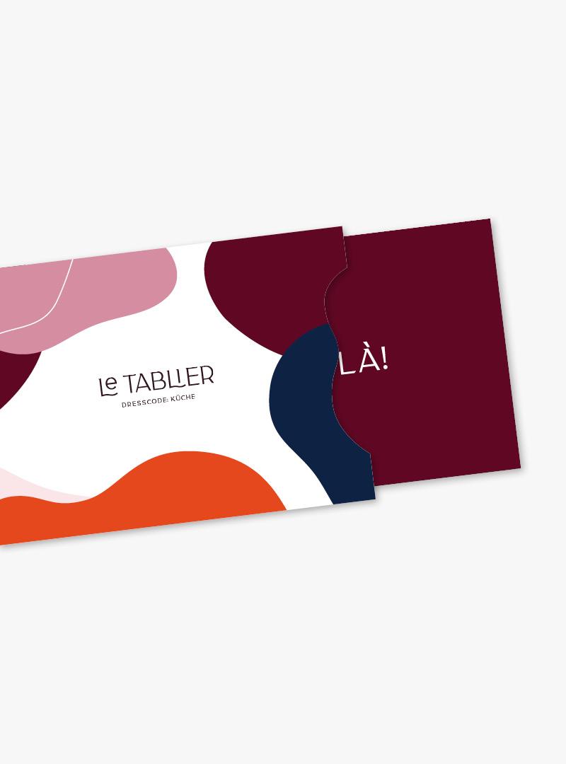 le tablier | Kuvert mit dunkelrotem Gutschein herausgeschoben