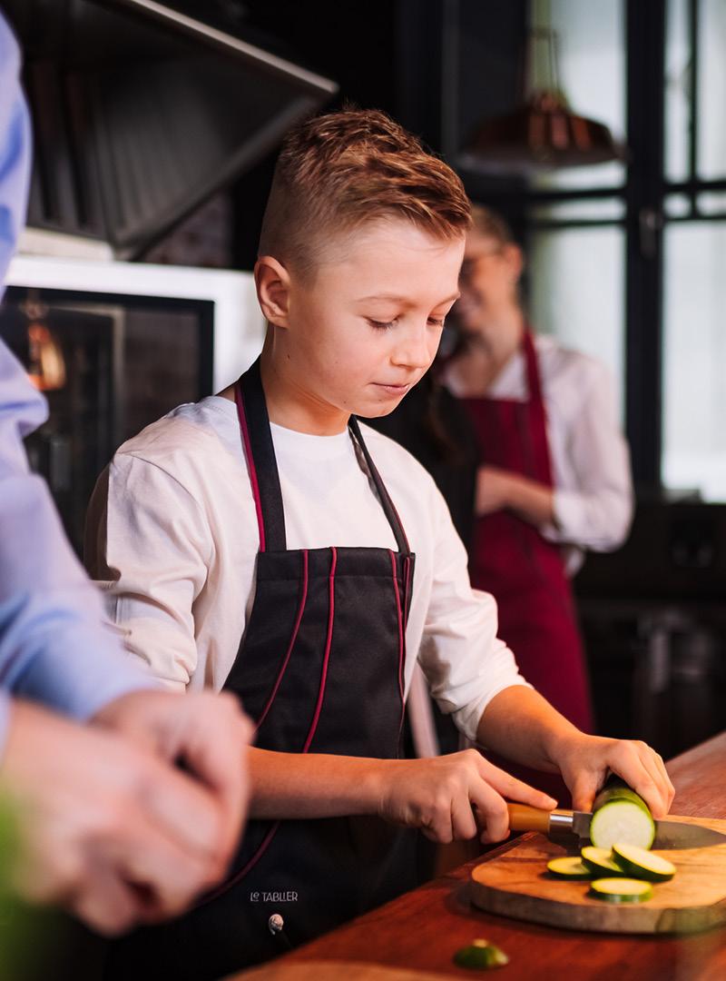 le tablier | blonder Junge in einer Küche mit schwarzer Schürze beim Scheiden von Gemüse