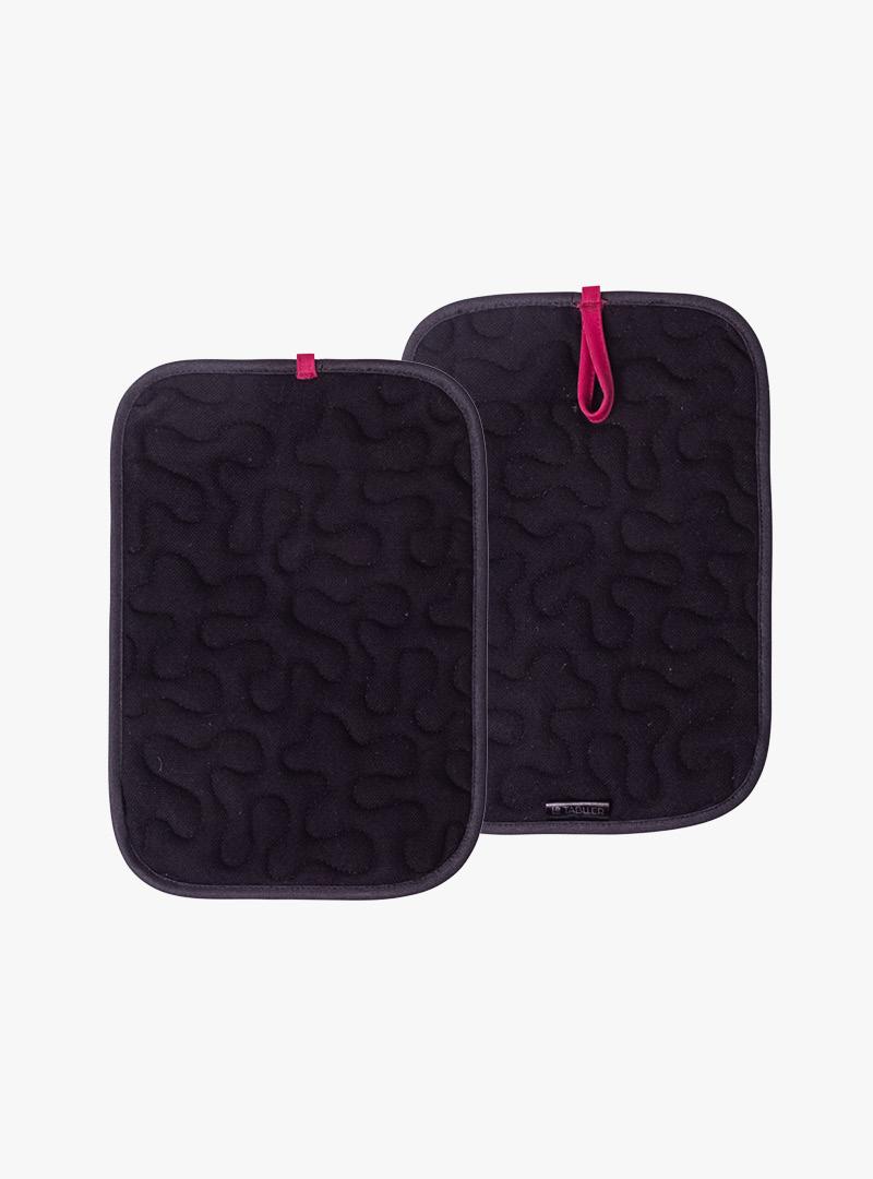 le tablier | zwei schwarze Topflappen mit roten Hänkeln und Muster