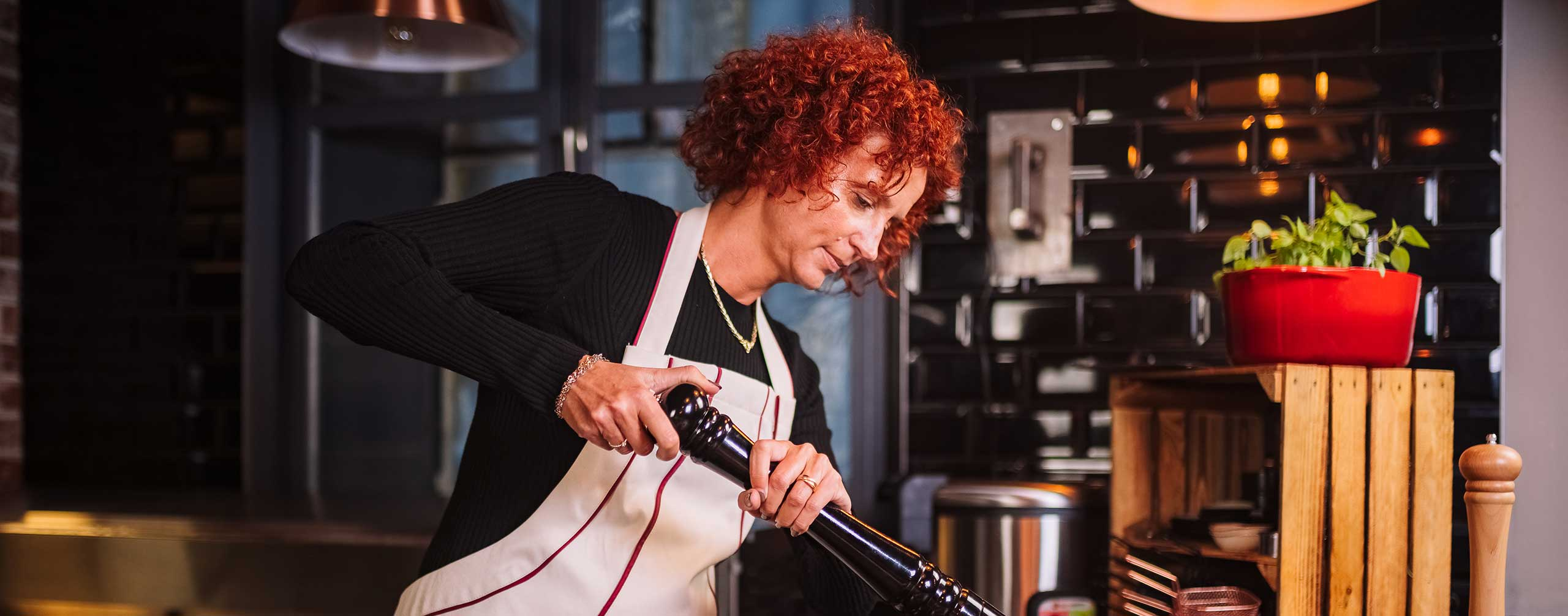 le tablier | rothaarige Frau beim Kochen in der Küche