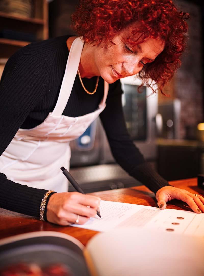le tablier   rothaarige Frau mit rosa Schürze beim Schreiben eines Rezepts