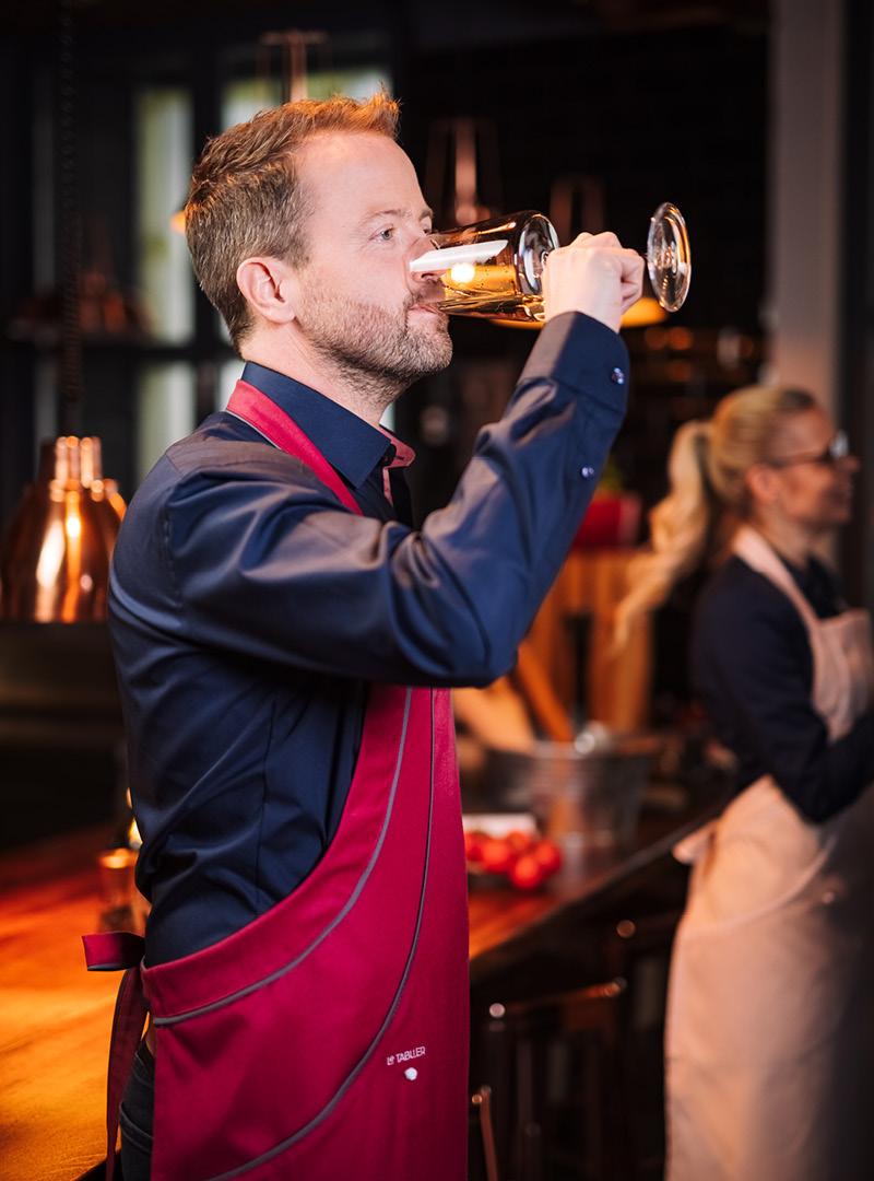 le tablier | Mann beim Weintrinken mit roter Schürze in einer Küche