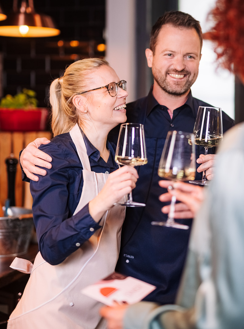 le tablier | blonde Frau mit Weinglas und rosa Schürze mit ihrem Mann