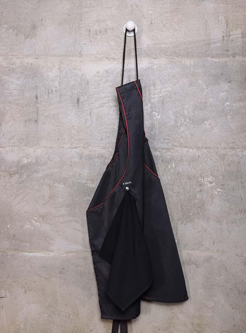 le tablier | schwarze Schürze an weißem Haken an Betonwand