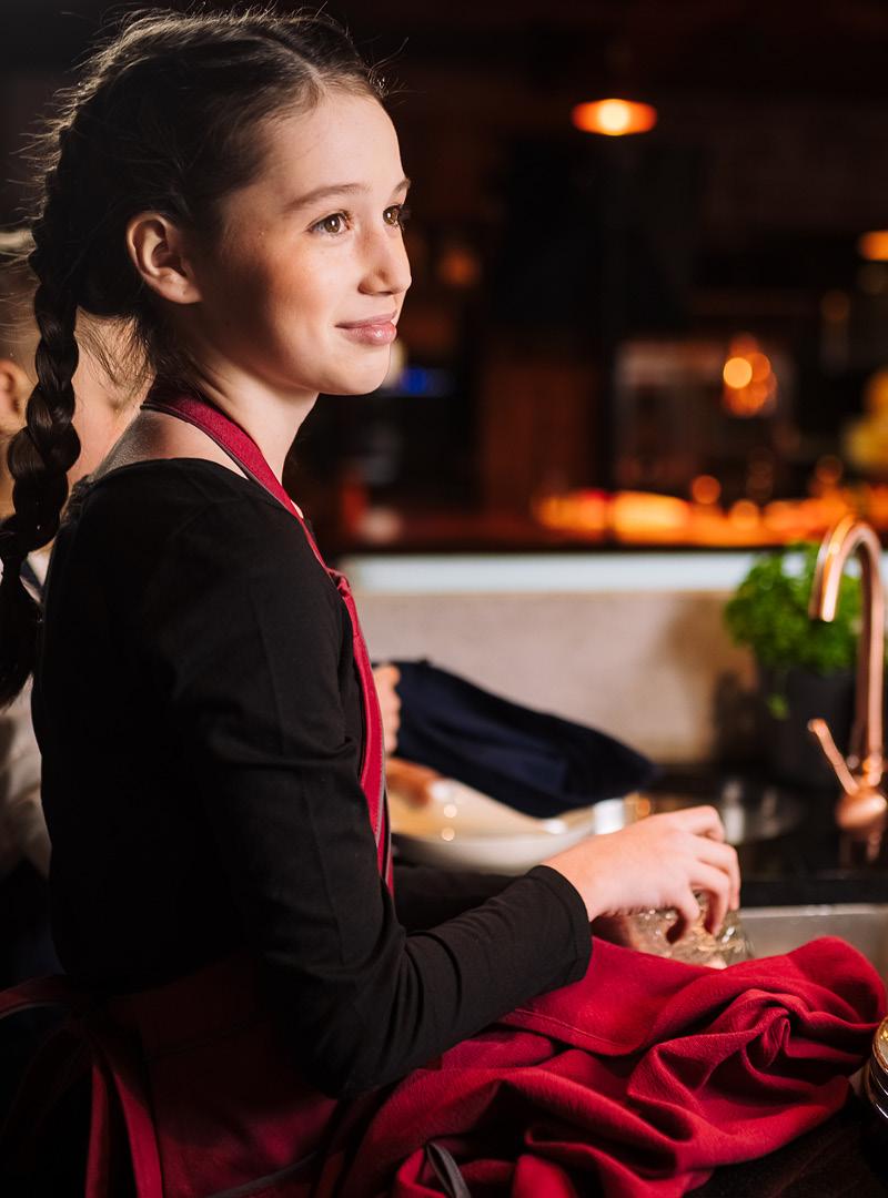 le tablier | schwarzhaariges Mädchen mit roter Schürze beim Abtrocknen