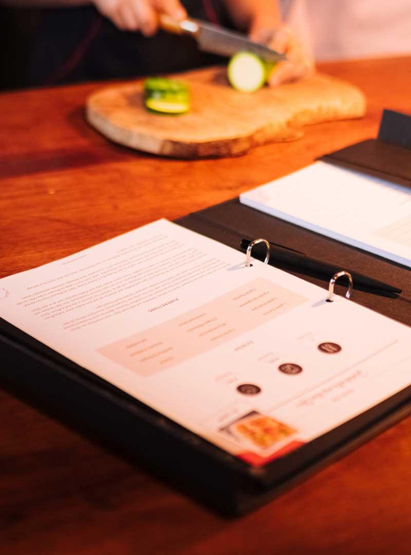 le tablier   geöffnetes Rezeptbuch auf einem Tisch